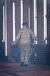 © Joel Goodman - 07973 332324 . No syndication permitted . 28/11/2013 . Manchester , UK . A man in army fatigues walks away from the house carrying a holdall and a metal frame . Scene at 17 Mellor Street in Eccles , Greater Manchester this evening (Thursday 28th November 2013) where police have cordoned off adjoining streets and evacuated houses following the discovery of a suspicious device .  Photo credit : Joel Goodman