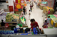 A supermarket employee arranges goods on the top shelf of an aisle in the Auchan supermarket in Nanjing, Jiangsu Province, China.