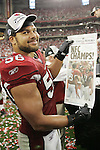 Arizona Cardinals linebacker Chike Okeafor smiles after reading the Arizona Republic's next day headline after defeating the Philadelphia Eagles for the NFC Championship on January 18th, 2009 at University of Phoenix Stadium in Glendale, AZ.