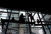 Silhouette Of Workers Welding A Building Structure From A Scaffolding At The Starbucks On Minzu Lu in Chongqing, China.  © LAN