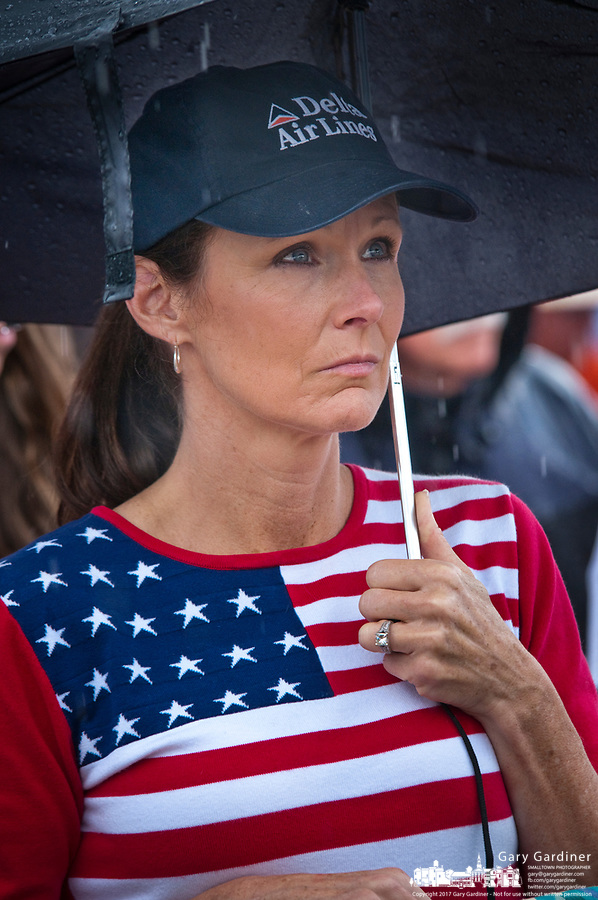 A woman wearing an airlines cap and a flag motif shirt stands in the rain at First Responders Park in Westerville, OH, during ceremonies marking the 10th anniversary of the attack on the World Trade Center