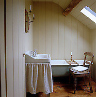 The walls of the small bathroom are panelled in tongue and groove