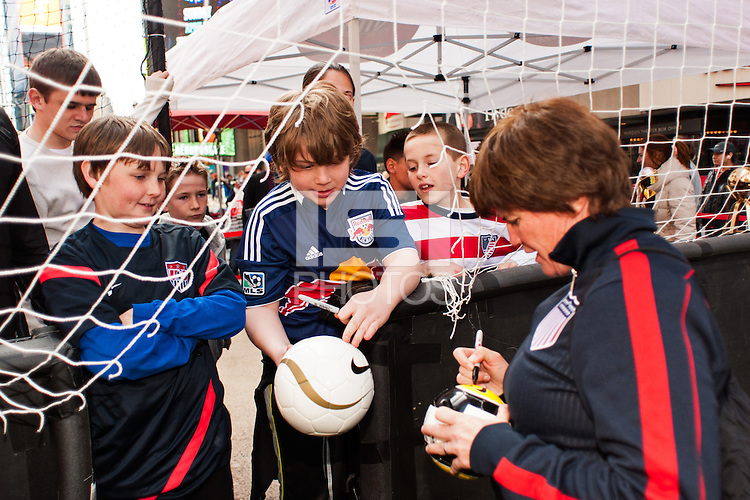 former women's national team player April Heinrichs signs autographs during the centennial celebration of U. S. Soccer at Times Square in New York, NY, on April 04, 2013.
