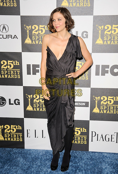 MAGGIE GYLLENHAAL.The 25th Annual Film Independent Spirit Awards at the LA Live Event Deck in Los Angeles, California, USA..March 5th, 2010  .full length black grey gray one shoulder dress hand on hip wrap low cut neckline tights.CAP/ROT.©Lee Roth/Capital Pictures