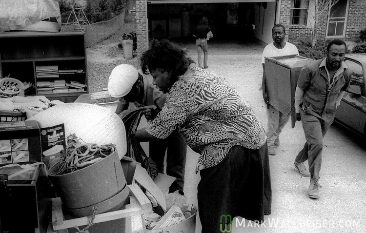 Photograph of a woman searching though her belongings at the street curb as workers carry her furniture from her home during her eviction in Tallahassee, Florida.