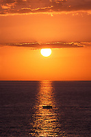 Sunset with small boat over water.