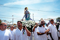 Groups of men carry religious statues and icons, including Saint Peter and Mary, through the streets of Gloucester, Massachusetts, USA, as part of a procession and parade during St. Peter's Fiesta.