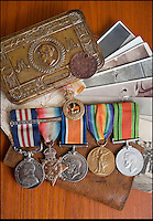 BNPS.co.uk (01202 558833)<br /> Pic: PhilYeomans/BNPS<br /> <br /> Family photos that saved him, Military medal (with bar) as well as the Mons Star, 1914 gift tin from Queen Mary (sent to all soldiers),leather wallet, dog tag and his map of the Passchendaele offensive from 1917.<br /> <br /> Saved by pictures of his loving family...<br /> <br /> An amazing tale of a heroes lucky survival through the entire First World War has been uncovered after his family revealed his remarkable tale to a local history group.<br /> <br /> Photos of loved ones that saved a soldier's life by stopping a piece of shrapnel aimed for his heart have come to light - complete with the holes the fragment left behind.<br /> <br /> Private William Taylor kept the nine pictures of his family in his wallet in his breast pocket during the entire four years of World War One.<br /> <br /> In a remarkable quirk of fate he survived a battle which left three quarters of his regiment dead or injured thanks to the stack of photos which took the impact of a shell blast.<br /> <br /> The projectile pierced the outer layer of his leather wallet and perforated eight of the nine photos.<br /> <br /> Luckily, the last picture of his younger sister Lilly stopped the fragment from going any further.