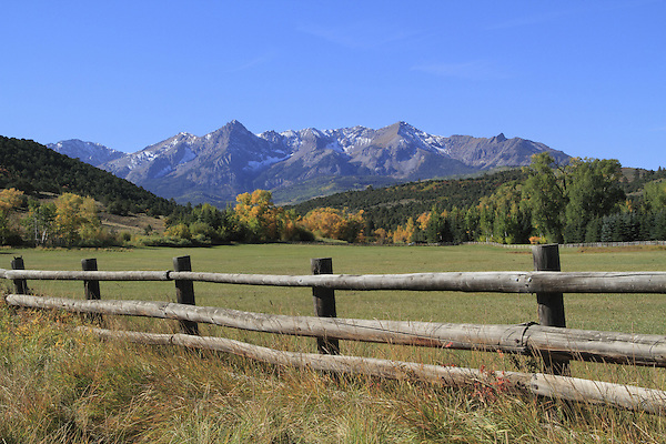 Wood fence and pasture with the Sneffels Range, Colorado.