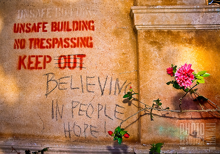"""Flowers grow near the modified message, """"Keep believing in people hope!"""" at the old Maui High School, Maui."""