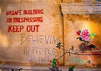 "Flowers grow near the modified message, ""Keep believing in people hope!"" at the old Maui High School, Maui."