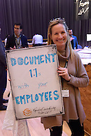 A smiling team member with her sign.