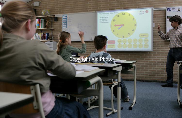 Foto: VidiPhoto..ACHTERBERG - De Willem Teelinckschool in Achterberg bij Rhenen werkt in alle klassen met een digitaal schoolbord. De school heeft de nieuwbouw aangegrepen om ook dit lesmateriaal te moderniseren. Voordeel van een digitaal schoolbord is dat het zowel op de ouderwetse manier als geheel computergestuurd gebruikt kan worden. Vier keer zo veel basisscholen als in 2006 werkten vorig jaar met digitale schoolborden, zo blijkt uit onderzoek. Op dit moment maakt 48 procent van de basisscholen gebruik van een of meer digitale schoolborden. In het voortgezet onderwijs is dat 60 procent. Van alle ict-voorzieningen is deze het meest gewild. Ruim driekwart van de scholen is van plan in de toekomst een digitaal schoolbord aan te schaffen.