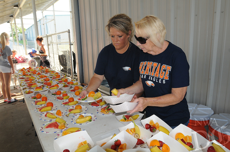 NWA Democrat-Gazette/FLIP PUTTHOFF<br /> HEALTHY TREATS<br /> Tricia Kitterman (left) and Jan Russell fix fruit plates Friday August 7 2015 for Rogers Heritage High School football players to eat after practice. Players get fruit and a salty treat when they take part in &quot;super practices&quot; that last longer than normal practice, Kitterman said. Moms and grandmothers of the players prepare the fruit plates.