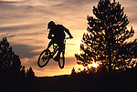A photo of a man jumping his bike while mountain biking at sunset near Truckee, CA.