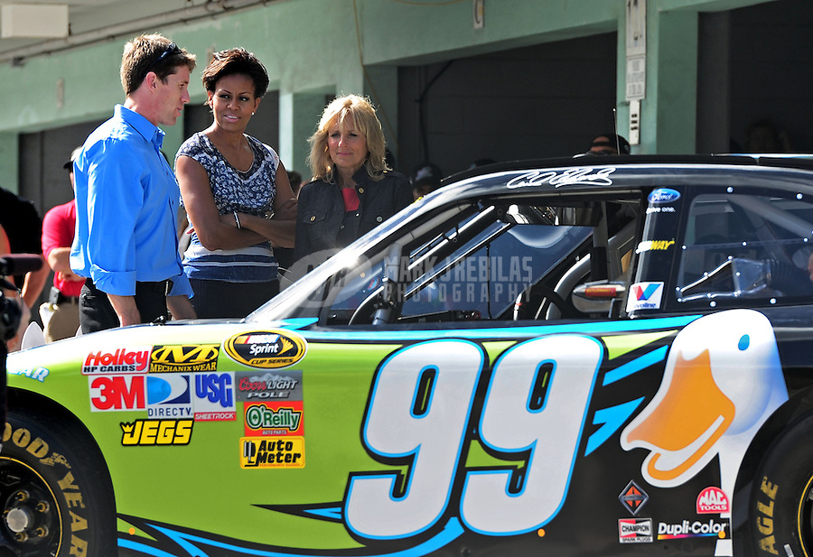 Nov. 20, 2011; Homestead, FL, USA; NASCAR Sprint Cup Series driver Carl Edwards (left) talks with first lady Michelle Obama (center) and Dr. Jill Biden in the garage area prior to the Ford 400 at Homestead Miami Speedway. Mandatory Credit: Mark J. Rebilas-