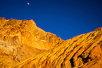 United States, California, Death Valley. Artist's Drive at the foot of the Black Mountains. Sunset with the Moon above the mountain.