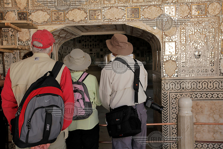 Tourists in Amber Fort. It was the ancient citadel of the ruling Kachhawa clan of Amber, before the capital was shifted to present day Jaipur. Amber Fort is known for its unique artistic style, blending both Hindu and Muslim (Mughal) elements.The fort borders the Maota Lake, and is a major tourist attraction in Rajasthan.