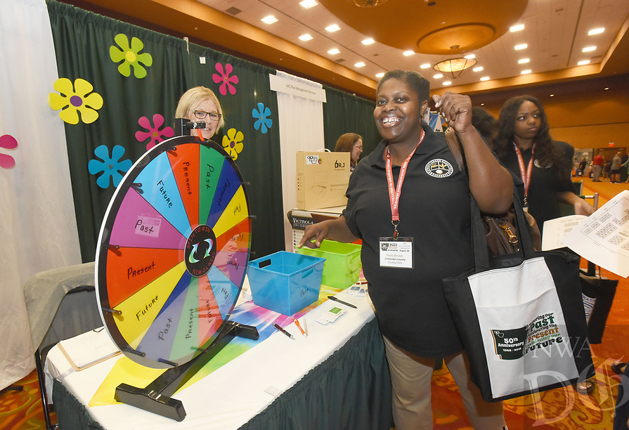 NWA Democrat-Gazette/FLIP PUTTHOFF <br />COUNTY CONFERENCE OPENS<br />Paula Brown, Crittenden County clerk, celebrates winning a prize on Wednesday Aug. 8 2018 during opening day of the Association of Arkansas Counties conference at the John Q. Hammons Center in Rogers. Officials from counties around the state opened the conference Wednesday with vendor exhibits and samples, breakfast and breakout meetings for various posts in county government such as county judges, sheriffs and assessors. The conference continues through Friday. U.S. Rep Steve Womack (R-Rogers) addressed the conference Wednesday. Gov. Asa Hutchinson will speak at 9 a.m. today. Aliyah was at the conference with her grandpa, James Ross of Miller County.