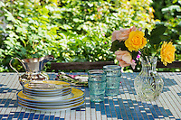 A garden table with a blue and white tiled top is used regularly for al fresco dining