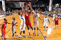 21 January 2012:  FIU center Brandon Moore (22) and guard-forward Dominique Ferguson (3) attempt to block a shot by FAU guard-forward Jordan McCoy (21) in the first half as the Florida Atlantic University Owls defeated the FIU Golden Panthers, 66-64, at the U.S. Century Bank Arena in Miami, Florida.