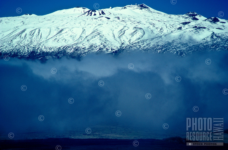 Summit of Mauna Kea seen from Mauna Loa, with observatories on top and clouds gathering in the saddle between the two volcanoes