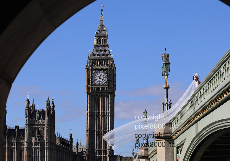 Pic shows: Chinese bride looks out over the Thames on a late sunny day in October with Big Ben and Westminster parliament in the background.<br /> <br /> As she paused between photos with her new groom he extra long white veil floated on the wind.<br /> <br /> <br /> <br /> <br /> Pic by Gavin Rodgers/Pixel 8000 Ltd 11.10.16