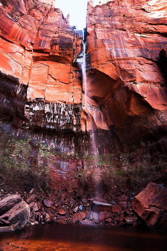 A waterfall cascades into Upper Emerald Pool in Zion National Park.