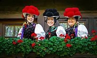 Germany, Baden-Wurttemberg, Kirnbach (Wolfach): three young women in famous Black Forest costume with red and black Bollenhat on the balcony of an original Black Forest farmhouse | Deutschland, Baden-Wuerttemberg, Ortenaukreis, Kirnbach (Wolfach): drei junge Frauen auf dem Balkon eines echten Schwarzwaelder Bauernhauses in der beruehmten Kirnbacher Tracht mit dem roten und schwarzen Bollenhut, die heute in der ganzen Welt als Schwarzwaelder Tracht bekannt ist
