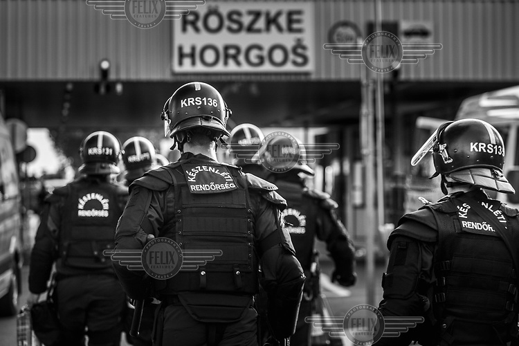 Riot police heading to the border crossing with Serbia to confront refugees trying to get into Hungary from Serbia, after Hungary closed its border with Croatia.