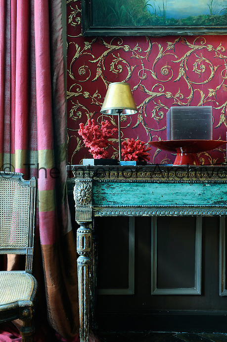 Two pieces of deep-pink coral create a stunning contrast set against ornate wallpaper curlicues and the distressed turquoise blue of an antique console table