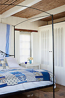 A country bedroom with a bamboo and beamed ceiling. The room is furnished with an iron four-poster bed with a blue and white bed patterned cover.