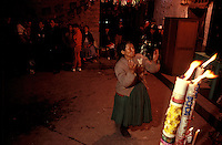 An Indian woman raises her hands in prayer below an altar laid out for the Virgin Mary in Cuzco. Created in the corner of a small café, the altar drew a small crowd on the eve of the Feast of the Pentecost.