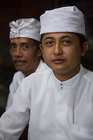 Bali, Indonesia.  Young Hindu Priest and a Member of his Community.  Pura Dalem Temple, Dlod Blungbang Village.