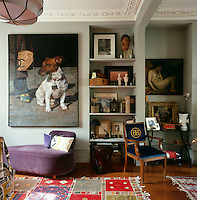 The sitting room is furnished with a mix of traditional and contemporary furniture. Paintings and other items are thoughtfully arranged on the walls and shelving. The polished wooden floor is set off by two colourful rugs