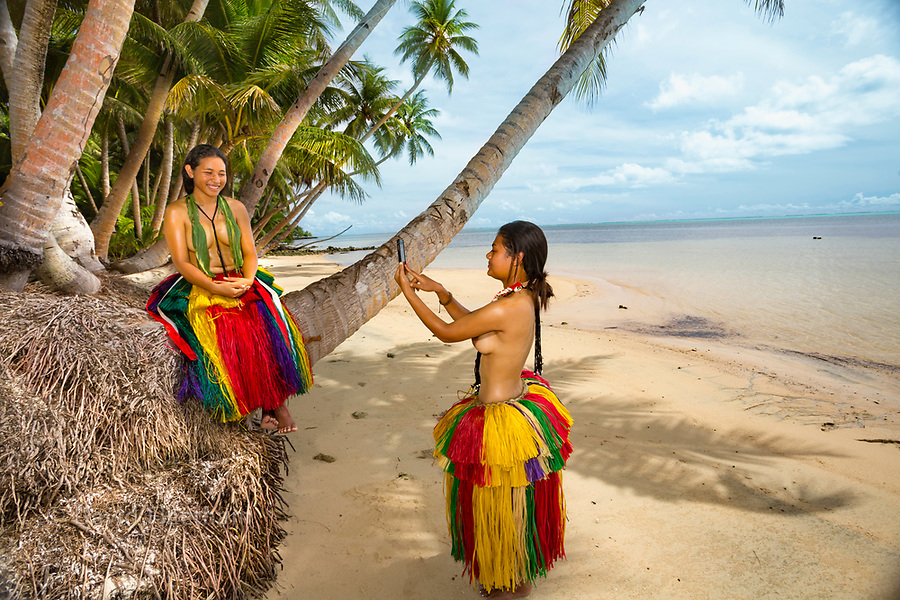 Two young girls (MR) is in traditional outfit for cultural cerimonies taking a photo with a smartphone on the island of Yap, Micronesia.