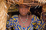 A Fulani girl stands in the doorway of a straw hut in the small village of Bele Kwara in southwestern Niger .  The Fulani people are primarily nomadic pastoralists who crisscross across the West African Sahel, leading their cattle, sheep, and goats in search of water and rich grazing grounds in a yearly cycle that has continued for centuries. In the past years, though, a large percentage of Fulani people have adopted a more sedentary lifestyle. While still holding onto their pastoralist roots, some families have also built permanent villages and begun to farm swaying fields of millet, sorghum, and corn...Bele Kwara is a tiny village of only about 100 people some 70 kilometers southwest of Niger's capital, Niamey. In the late 1990s, the village of Bele Kwara was home to only 40 people. Now, in 2007, it has grown to 100, as the family pastoralists have come back home to settle. Rather than living in a hut made of sheets of weaved grass that could easily be moved from one place to another in the pastoralist tradition, this girl lives in a permanent mud brick hut with a straw roof.
