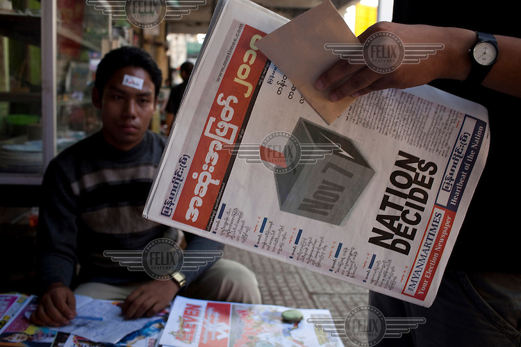 A newspaper vendor sits with a sticker attached to his face that reads iVote, while a customer reads an election special newspaper for sale at a newsstand ahead of Burma's first multi-party elections since 1990. However, the main pro-democracy party, the NLD (National League for Democracy), boycotted the poll and other opposition groups have alleged widespread voting fraud.