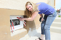 Christine Quedenfeld zeigt die Schäden an den Kellerfenstern und der Haustür vom Storchenangriff
