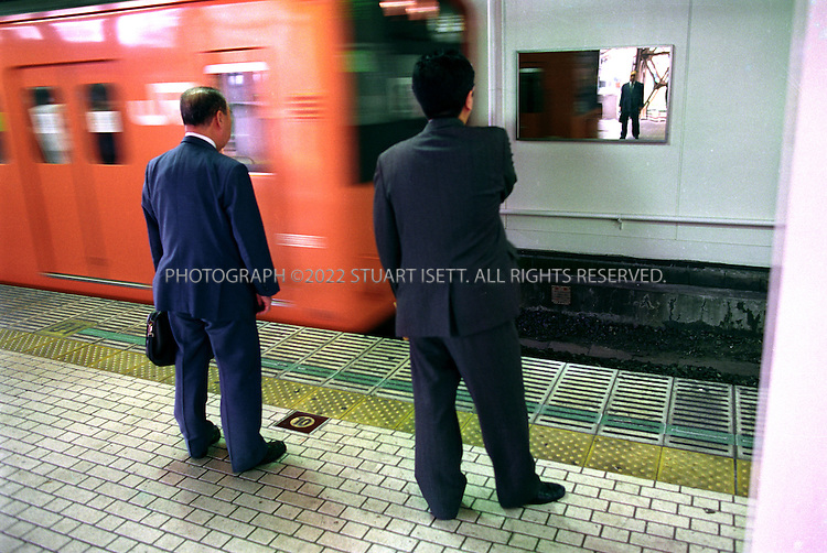 8/12/2000?Tokyo, Japan.Japanese salarymen stand on the platform of a Japan Railways station that has hung mirrors to stop depressed businessmen from jumping on the tracks. A surge in suicides since the collapse of Japan's economic bubble has forced officials to such drastic measures.All photographs ©2003 Stuart Isett.All rights reserved.This image may not be reproduced without expressed written permission from Stuart Isett.