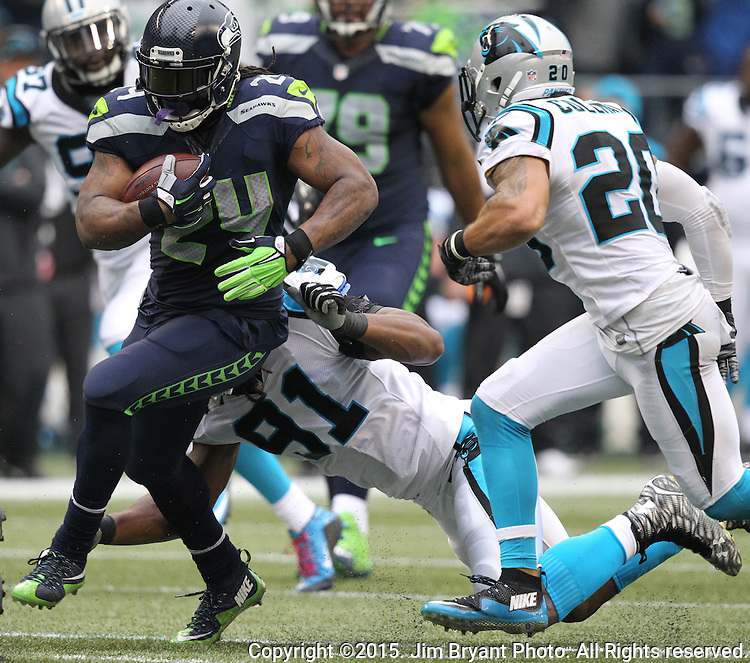 Seattle Seahawks  running back Marshawn Lynch (24) breaks a tackle by Carolina Panthers defensive end Ryan Delaire (91) and safety Kurt Coleman (20) at CenturyLink Field in Seattle on October 18, 2015. The Panthers came from behind with 32 seconds remaining in the 4th Quarter to beat the Seahawks 27-23.  ©2015 Jim Bryant Photography. All Rights Reserved.