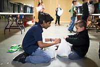 NWA Democrat-Gazette/CHARLIE KAIJO Jeruel Gangavarapu, 11, of Bentonville (left) helps Christian Richey, 4, of Bentonville tie a snack pack, Thursday, March 22, 2018 at the Samaritan Community Center in Rogers. <br />