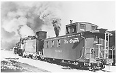 Side-end view of long caboose #04343 with locomotive, flying herald, in snow.<br /> D&amp;RGW