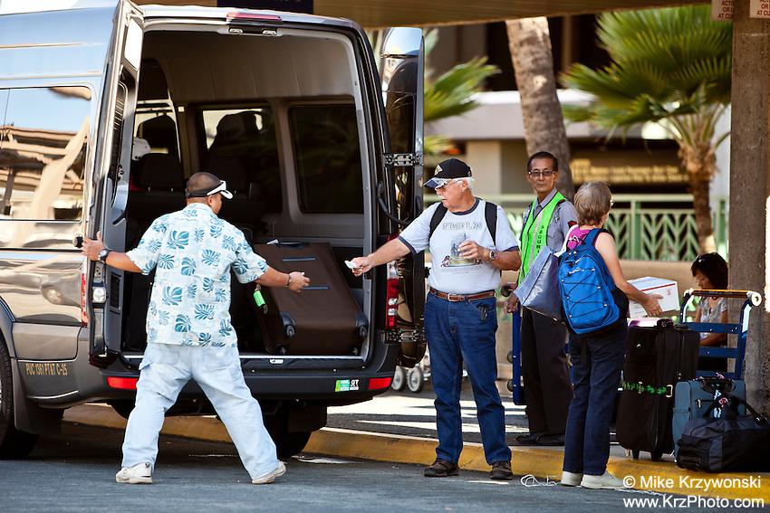 Caucasian man handing shuttle van driver a tip at the Honolulu International Airport, Oahu, Hawaii