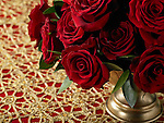 A bouquet of red roses in a vase on a red and gold tablecloth.