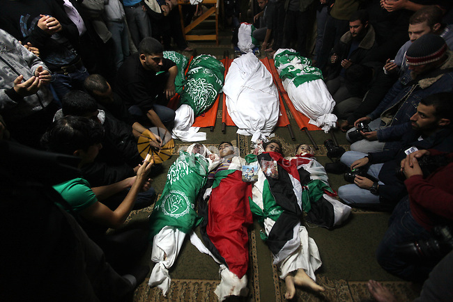 Palestinian mourners gather around the bodies of the al-Dallu family during their funeral in Gaza City, 19 November 2012. Nine members of the al-Dallu family died when Israeli forced hit their building in Gaza City one day ago. Media reports state that Israeli forces were on monday targeting the Palestinian homes and other buildings in its bombardment of the Gaza Strip, as the combined death toll in six days of airstrikes and rocket attacks climbed to nearly 100. Photo by Majdi Fathi