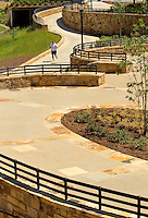 Photography of the Midtown Park area of Charlotte NC's Little Sugar Creek Greenway, a public park with more than 19 miles of trails and land connectors. Charlotte designed the Sugar Creek Greenway with the goal of connecting neighborhoods, landmarks and activities and increasing the Queen City's pedestrian-oriented activities. The Midtown Park section, located next to the Metropolitan mixed-use development, is a one-acre site that until recent years held a gas station. Today the park uses stone, artwork and other materials to bring new life to the area.