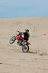red Dirt bike wheelie on the Oregon Dunes