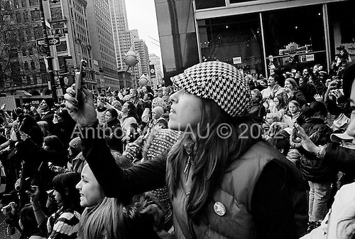 New York, New York<br /> November 26, 2009<br /> USA<br /> <br /> The Macy's Thanksgiving Day Parade in mid-town Manhattan, as children's cartoon character shaped balloons float through the skyscrapers on 6th Avenue and 42nd Street. Crowds gather to mark the beginning of the Christmas season.