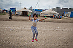 A young female Syrian refugee uses a piece of rope to skip near her tent in the Domiz refugee camp in Iraqi-Kurdistan. The camp, run by the UNHCR and International Rescue Committee, is home to around 4,500 refugees who have fled from the ongoing Syrian civil war with up to 400 new inhabitants arriving every day.  Built on the site of a former Iraqi Army base that was bombed during the 2003 Coalition forces invasion of Iraq, the camp was cleared of cluster bombs and unexploded ordnance by the Mines Advisory Group (MAG), a demining NGO working in Iraqi-Kurdistan.